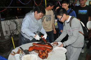 Master Sam Lau chops and distributes suckling pig
