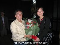 Accepting flowers presented by the staff of China Wushu Association
